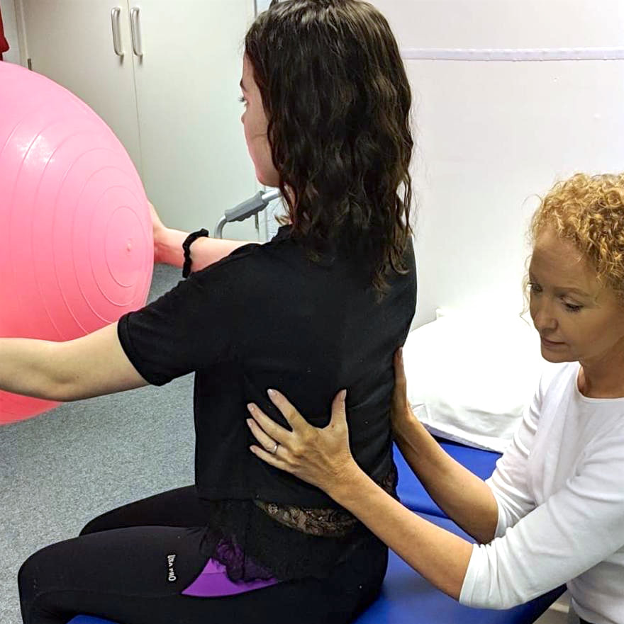 Claire Evans with patient holding big pink ball