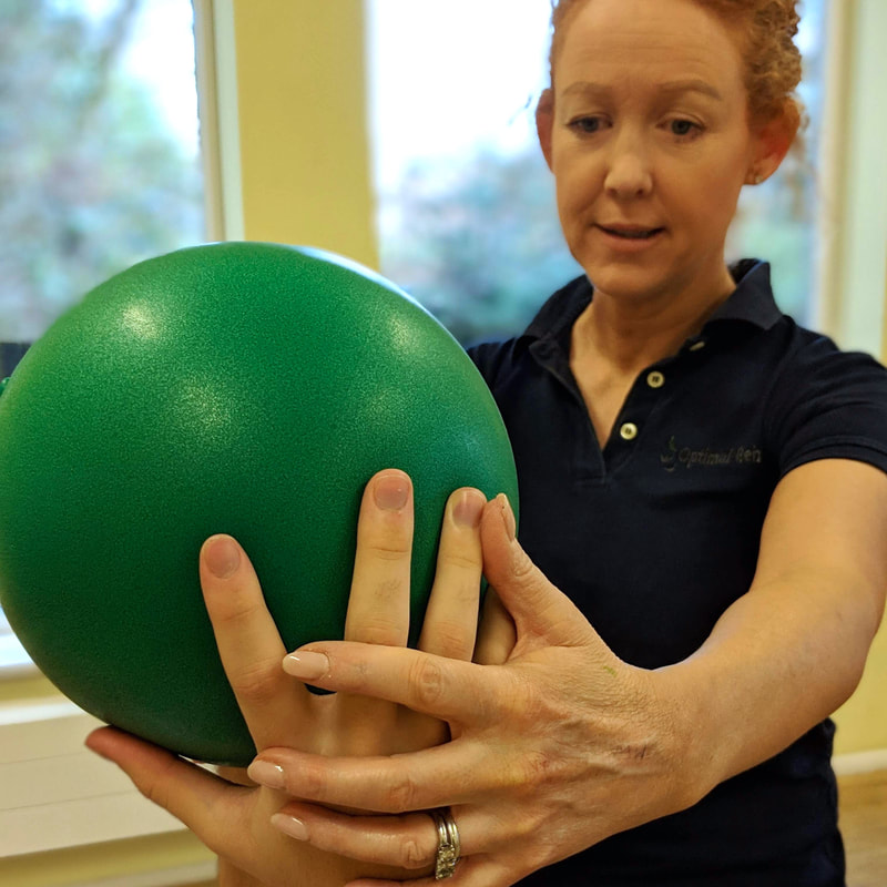 Claire Evans with patient holding small green ball